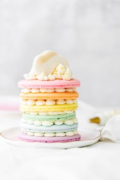 Rainbow themed french macaron cake filled with marshmallow frosting and lemon curd. Dairy and gluten free. Pretty dessert ideas for parties and birthdays.