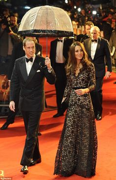Belle of the ball: Kate Middleton lead the way at the War Horse premiere in Leicester Square with a stunning floor-length gown, as Prince William shielded her from the rain