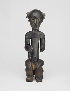 Figure from a Reliquary Ensemble: Seated Male Holding Horn Date: 19th century (before 1913) Geography: southern Cameroon, Lokoundje valley Culture: Fang peoples, Ngumba group Medium: Wood, metal strips Dimensions: Height: 23 5/8 in. (60 cm)