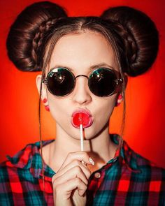 Girl wearing sunglasses & holding a red lollipop