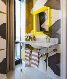 I am crazy about this patterned wallpaper and the bright yellow mirror in this powder room - Tobi Fairley Interior Design