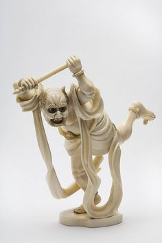 Ivory okimino in the shape of a demon holding a stick and with a long banner draped around the body.