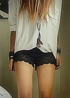 white top, cuffed sleeves. feather/bead necklace. black lace shorts. bracelets.