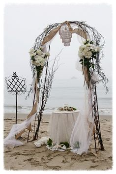 Romantic Wedding Arch $300 - Includes two large fresh flower arrangements, white tulle, white chandelier, burlap ribbon, ceremonial table dr...