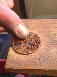 "Thornhill explians, ""Once the design is on the coin we drill a small hole with a 0.8 mm drill bit and then we cut out that section and then drill again and so on; some designs have up to 40 holes."" ... Image: Elaborate carved coins (© Rex Features)"
