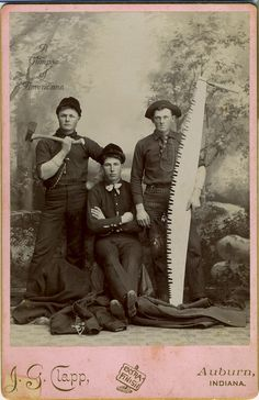 View of a three loggers, one holds ax, another a large saw.  Clapp, Auburn, Indiana photographer's imprint.