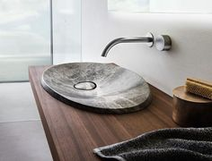 This modern bathroom sink made from natural stone sits on a floating wood vanity and has a simple stainless steel faucet.