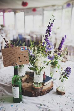 Wooden Slab with jam jars wrapped in lace ribbon and filled with wild flower stems  | Outdoor Ceremony | Festival Theme Wedding | Image by Anna Hardy Photography. | http://www.rockmywedding.co.uk/wildflowers-at-wedfest/