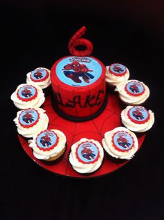 Spiderman cutting cake and cupcake board