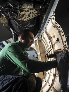 "ARABIAN SEA (Aug. 30, 2013) Aviation Machinist's Mate 2nd Class Alex Alegre, of Visalia, Calif., assigned to the ""Argonauts"" of Strike Fighter Squadron (VFA) 147 cleans corrosion off an F/A-18E Super Hornet from the ""Argonauts"" of Strike Fighter Squadron (VFA) 147 in the hangar bay on board the aircraft carrier USS Nimitz (CVN 68). Nimitz Strike Group is deployed to the U.S. 5th Fleet area of responsibility conducting maritime security operations and theater security cooperation efforts. (U...."