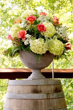 Rustic yet elegant arrangement of roses, hydrangeas and fern sitting stop a wine barrel.