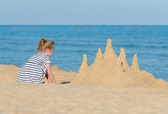 Little girl with sand castle on the beach. ...  activity, back, beach, build, castle, castles, caucasian, child, childhood, coast, coastline, cute, enjoying, girl, happy, holiday, kid, leisure, lifestyle, little girl, ocean, outdoor, play, playful, playing, sand, sandcastles, sculpture, sea, shore, summer, sun, travel, tropical, vacation, water, young, youth