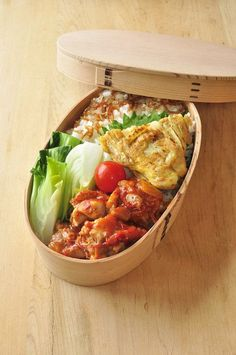 Bento box featuring tomato chicken, Spanish omelette, sauteed bok choy, and white rice topped with crispy fried shallots