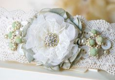 This lace cuff bracelet features a handmade fabric flower in mint green and ivory white hues, vintage millinery flowers, vintage buttons and pearl beads. A uniq