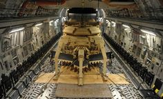 The belly of a Boeing C-17 Globemaster III carrying a 64-ton, 42-foot-long US Army Assault Breacher which is basically an M1A1 Abrams tank outfitted with minesweeping equipment.