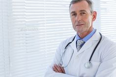 Confident male doctor looking at camera with arms crossed in medical office - Stock Photo - Images