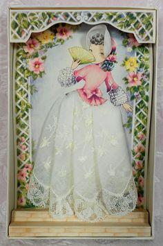 Vintage paper doll handkerchief dress on lattice gazebo graphic card