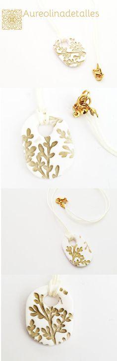 Colgante realizado en base de polymer clay  blanca con dibujos de hojas de color oro.