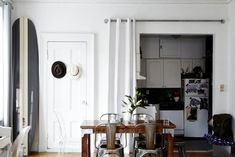 Kristin Barone, gray and white striped surfboard, white curtain hides kitchen, metal tolix stools, Remodelista