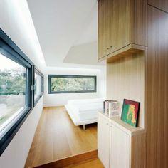Le bloc de bois blond présent au centre de la maison structure l'espace. Les chambres avec leurs fenêtres en longueur permettent à toute la famille de vivre au plus près de la nature. Plus de photos sur Côté Maison http://petitlien.fr/7az8