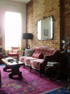 'Gidget's Fuschia, Black & Blue' - Apartment Therapy - vintage mirror & sofa  -- I love the sofa and mirror against the brick wall.