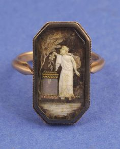 A VICTORIAN MOURNING RING. Circa 1800. The octagonal elongated frame enclosing gentleman holding flower under weeping willow tree infront of inlaid mother of pearl tombstone, the background with interwoven hair, mounted in rose gold.