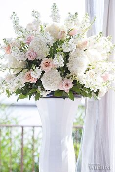 This is a beautiful outdoor display for entrance to wedding ceremony. White Hydrangea, White and Blush Roses and White Dendrobium Orchids. Need one of each side of back of chair aisles.