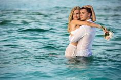 Happy newlywed couple standing in water. Maldives Islands.