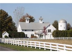 white barn with matching white silo...