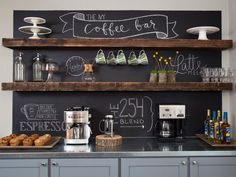 The coffee bar features cabinets in soft gray, a sleek metal countertop, floating shelves from reclaimed wood and a chalkboard backing for unleashing creativity.