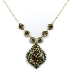 Miguel Ases beaded necklace pendant. Looks like brick stitch in different shapes and sizes around the focal bead