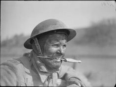 Portrait of a soldier from No. 3 Commando holding his fighting knife between his teeth, at Largs in Scotland, 2 May 1942.