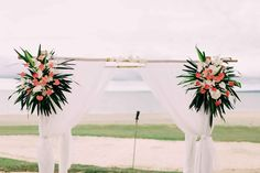 Beautiful tropical colourful flowers on a white draped bamboo wedding ceremony arch. Perfect for a Fiji beach wedding. Arch by 'Party & Event Hire Fiji' a division of 'Fiji Weddings'. ©Nadi Bay Photography (Fiji) by Laurence Beddoes.