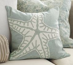 Starfish Embroidered Pillow Cover-A single starfish formed with a cotton appliqué and hand-stitched crewel embroidery spreads across a soft ocean blue ground. The design's fabric reveals its naturally threaded edges, creating added texture and depth.#potterybarn