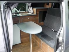 NV200 camper van interior conversion showing belted rear seats for two