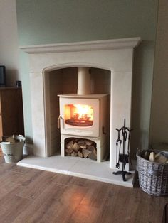 Our woodburner #love Charnwood C7 in Almond with log store. Portland stone fireplace surround.