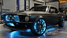 West Coast Customs took a 2012 Ford Mustang and retrofitted it with a 1967 Mustang fastback replica body. They painted the car matte black, and decked it out with neon blue lights in the grill and around the rims...