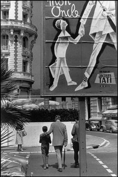 CANNES, France—Jacques Tati and Alain Bercourt walk toward the Hotel Carlton, which bears a poster for Tati's Mon Oncle, playing at the Cannes Film Festival, 1958. © Henri Cartier-Bresson / Magnum Photos
