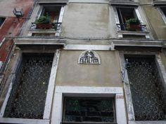 Op de gevel van de vroegere Scuola di Santo Stefano in het smalle straatje tegenover de ingang van de gelijknamige kerk, een onopvallend maar aandoenlijk tafereeltje uit het midden van de vijftiende eeuw.