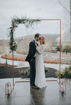 Copper pipe ceremony arch with wedding greenery.  Perfect for a simple winter wedding.  #winter #wedding #winterwedding #outdoorwedding