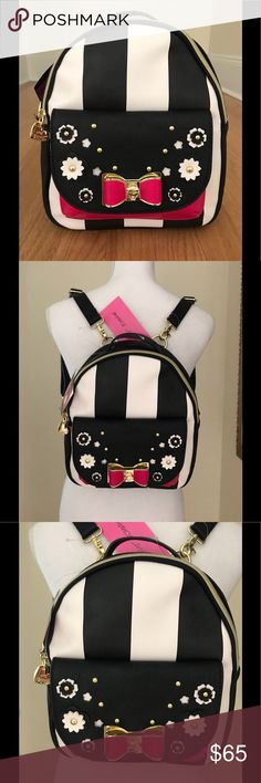 Betsey Johnson NWT Conv. Blk/Wh. Striped Backpack New With Tags, Betsey Johnson Black & White Striped Convertible Backpack. The Backpack Features A ZipTop Closure W/ A Betsey Heart Charm. The Front Pocket Has A Magnetic Snap Closure & Is Detailed With A Dk. Pink And GoldToned Bow, Along With Black & White Flowers & Gold Studs. The Interior Is Floral & Has 1 Zip Wall Pocket & 2 Media Wall Pockets. The Adjustable Straps Allow The Backpack To Be Converted To A Shoulder Or CrossBody Bag…