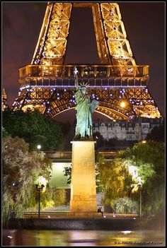 """The Statue of Liberty in Paris, France is near the Grenelle Bridge on the Île aux Cygnes, a man-made island in the river Seine. Inaugurated on July 4, 1889, it looks southwest, downriver along the Seine. Its tablet bears two dates: """"IV JUILLET 1776"""" (July 4, 1776: the United States Declaration of Independence) like the New York statue, and """"XIV JUILLET 1789"""" (July 14, 1789: the storming of the Bastille)."""