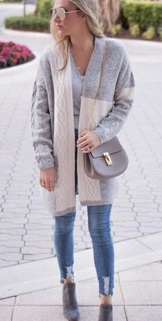 women's heather gray cardigan and distressed blue-washed jeans with pair of brown leather mid-calf boots