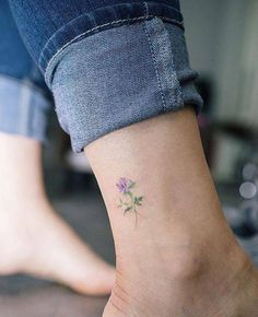 Small purple rose tattoo on the ankle.