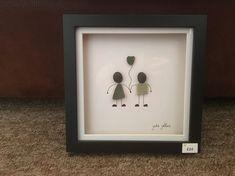 Beautiful Beachcombing Art Picture Of boy and girl with green glass heart balloon, using seacrockery, pebbles and seaglass 18 x 18 cms black frame