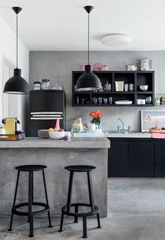 A pair of black Muuto pendant lights hang over a pair of black stools. The black fridge and cabinetry behind also look stunning against the ...