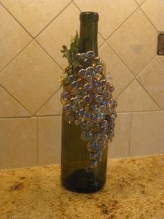 Glass stones and marbles on a wine bottle with a grape leaf stem to make a bunch of grapes.  Can display as is or drill a hole in the back to thread a short string of holiday lights through.