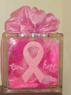 This is a lighted glass block thats adorned with feathers on the inside and has a pink ribbon on the outside with words cure and hope. Its adorned with a pink ribbon on top. Breast Cancer Party, Breast Cancer Wreath, Breast Cancer Crafts, Breast Cancer Support, Breast Cancer Awareness, Pink Ribbon Crafts, Breast Cancer Jewelry, Pink Light, Glass Blocks