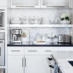 Style at Home - kitchens: white cabinets, white shaker cabinets, shaker front cabinets, shaker front cabinetry, nickel hardware, contemporary polished nickel hardware, black counters, glossy black countertops, honeycomb marble tiled backsplash, mini hex marble tile backsplash, mini marble hex tile, espresso maker, espresso machine, chrome espresso machine, chrome toaster, glass canister, stainless steel floating shelf, floating shelf, kitchen floating shelf, frosted glass kitchen cabinets…