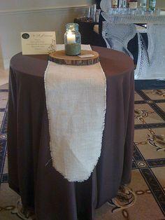 brown tablecloth with burlap runner, log slice, & blue mason jar